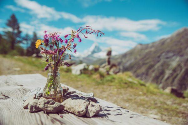 Blumenvase auf Holztisch in den Bergen