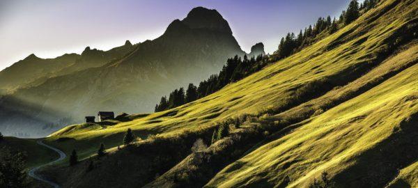 Ein Weg führt im frühen Morgenlicht an einem steilen Berghang vorbei