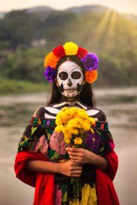 Trauern international Frau mit geschminktem Gesicht und Blumen