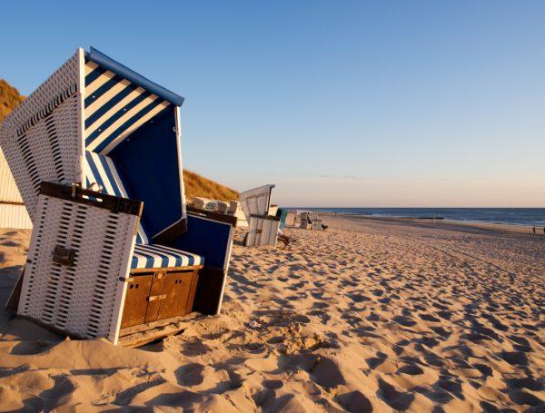 Ein blauweiß gestreifter Strandkorb am Sandstrand
