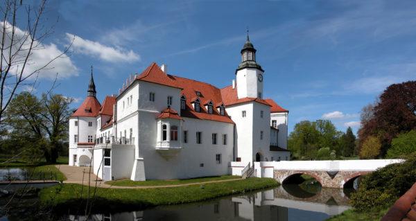 Weißes Schlosshotel mit Wassergraben